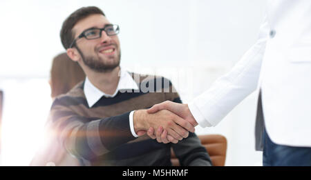 handshake between colleagues in the workplace - Stock Photo