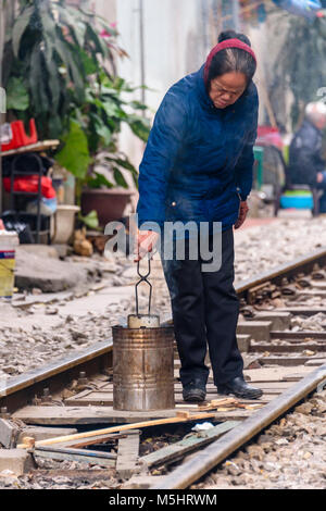 A woman cooks a meal using a metal stove and a fire in the middle of 'Hanoi Train Street', a narrow street in the - Stock Photo