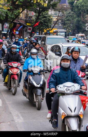 Heavy traffic, mainly scooters, travel at speed along a street in Hanoi, Vietnam.  Many people wear face masks to - Stock Photo