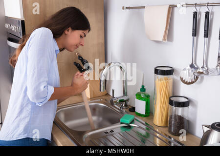 Side View Of A Young Woman Using Plunger In Blocked Kitchen Sink - Stock Photo