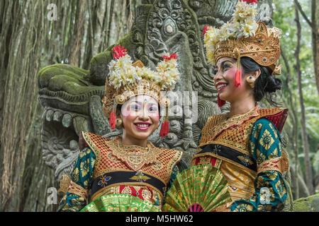 Two smiling dancers in traditional attire, Sacred Monkey Forest Sanctuary, Ubud, Bali, Indonesia - Stock Photo