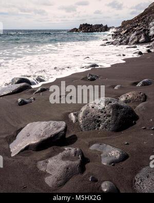 Salinas de Fuencaliente, La Palma. Canary Islands Spain.  Waves crashing on to the lava beach.  Some large lava - Stock Photo