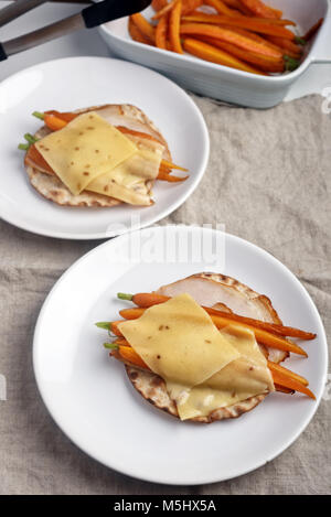 Sandwiches with ham, crisp bread, sliced cheese, and roasted carrots - Stock Photo