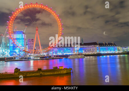 London, United Kingdom, February 17, 2018: UK skyline in the evening. Ilumination of the London Eye and the buildings - Stock Photo