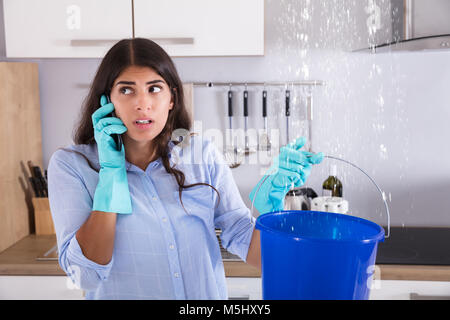 Woman Calling Plumber While Collecting Water Leaking From Ceiling Using Bucket - Stock Photo
