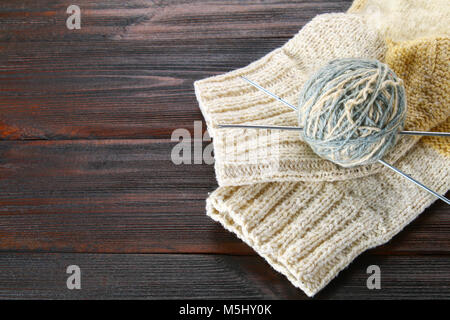 A ball of wool with knitting needles and knitted socks on a wooden table. Needlework - Stock Photo