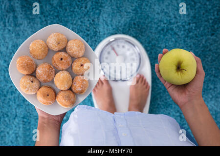 High Angle View Of A Person Holding Cookies And Apple Standing On Weighing Scales - Stock Photo