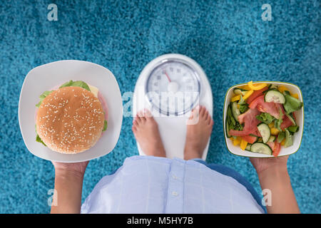 High Angle View Of A Person Holding Burger And Salad Standing On Weighing Machine - Stock Photo