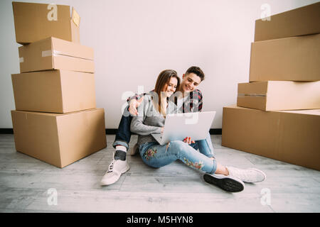 Young couple in love sitting on the floor of their new apartment, planning redecoration and searching for ideas - Stock Photo