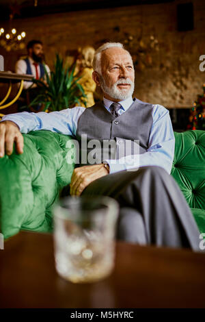 Portrait of elegant senior man sitting on couch in a bar - Stock Photo