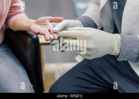 Pharmacist measuring blood sugar of customer in pharmacy - Stock Photo