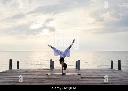 Yoga instructor standing upside down on hands while doing yoga against sunset and sea. Kep, Cambodia. - Stock Photo