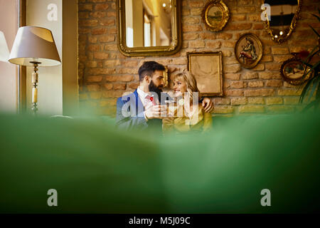 Elegant couple with drinks sitting on couch embracing - Stock Photo