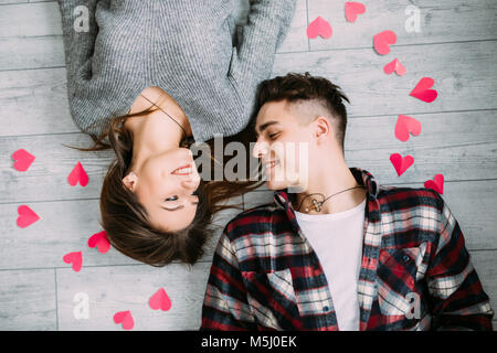 Side above top view photo of excited charming romantic gentle tender with toothy smile lovers lying on the grey - Stock Photo