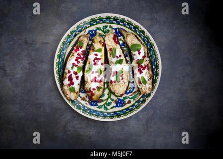 Filled aubergine, couscous, yogurt sauce, mint and pomegranate seeds - Stock Photo