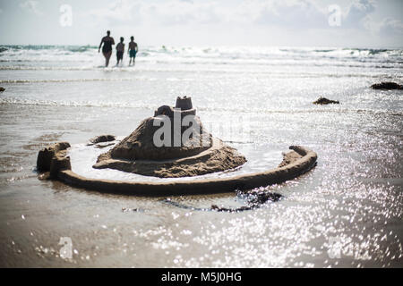 France, Normandy, Portbail, Contentin, sand castle on the beach and family in background - Stock Photo