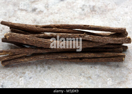 Bunch of liquorice sticks on a marble cutting board - Stock Photo