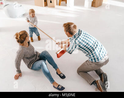 Father and daughter having fun with a broom in a loft - Stock Photo