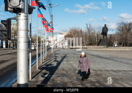 A woman walks on a central Lenin Square in Donetsk, DPR flags can be seen on the top. - Stock Photo