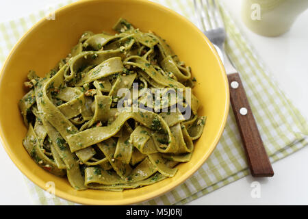 Spinach pasta with pesto sauce in a yellow bowl - Stock Photo