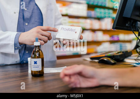 Pharmacist explaining medicine to customer in pharmacy - Stock Photo
