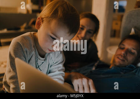 Family using laptop on the couch in the dark - Stock Photo