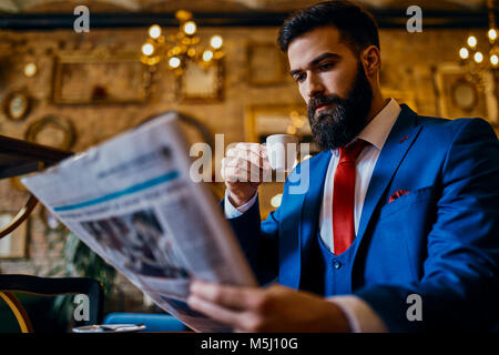 Elegant man drinking coffee and reading newspaper in a cafe - Stock Photo