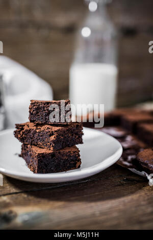 Stack of three homemade brownies on plate - Stock Photo