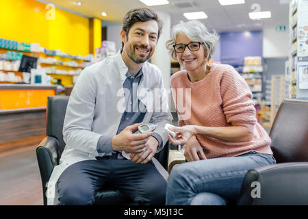 Portrait of smiling pharmacist and customer with blood sugar meter in pharmacy - Stock Photo