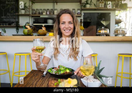 Portrait of smiling woman holding glass of wine in a cafe - Stock Photo