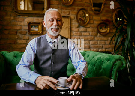 Portrait of elegant senior man sitting on couch in a cafe smiling - Stock Photo