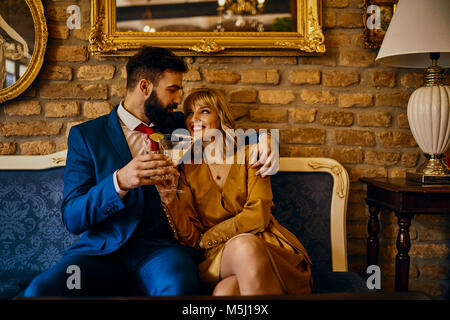 Happy elegant couple with drinks sitting on couch embracing - Stock Photo