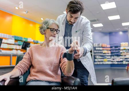 Pharmacist taking blood pressure of customer in pharmacy - Stock Photo