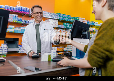 Customer paying cashless in a pharmacy - Stock Photo