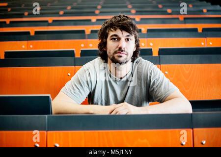 Portrait of student in auditorium at university - Stock Photo