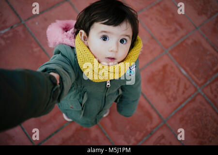 Portrait of little girl holding mother's hand looking up - Stock Photo