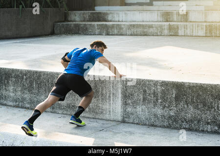 Athlete doing push-ups in the city - Stock Photo