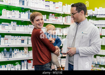 Pharmacist advising mother with son in pharmacy - Stock Photo