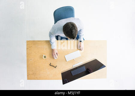 Businessman working at desk in office seen from above - Stock Photo