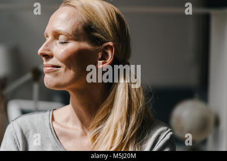 Portrait of smiling woman's face in sunlight - Stock Photo