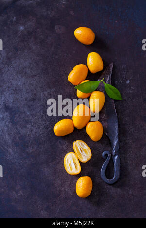 Sliced and whole kumquats, leaves and old knife on rusty ground - Stock Photo