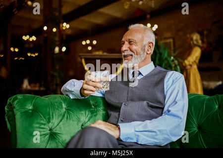 Portrait of elegant senior man sitting on couch in a bar holding tumbler - Stock Photo