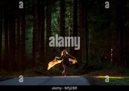 Young woman holding blanket running on country road through forest - Stock Photo