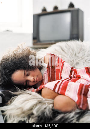 Portrait of little girl sleeping on arm chair in living room - Stock Photo