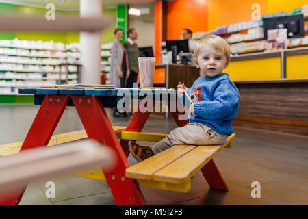 Little boy sitting on bench in pharmacy with parents in background - Stock Photo