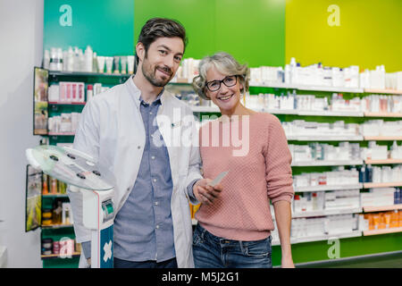 Portrait of smiling pharmacist with customer at sclaes in pharmacy - Stock Photo