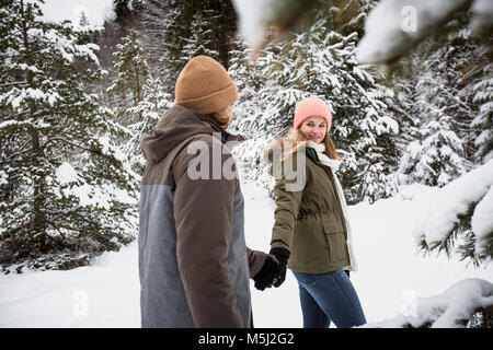 Couple walking in winter forest - Stock Photo