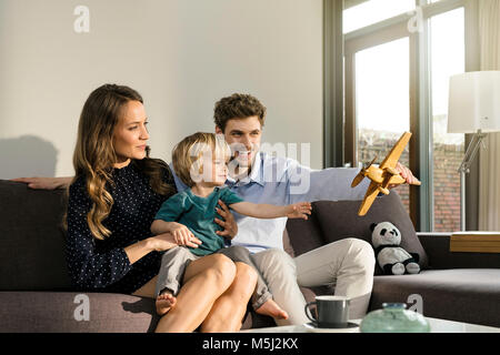 Happy parents and son playing with wooden toy plane on sofa at home - Stock Photo