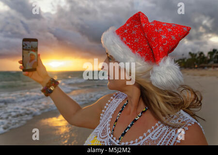 Carribean, Dominican Republic, Punta Cana, woman with Christmas cap taking selfie on the beach - Stock Photo