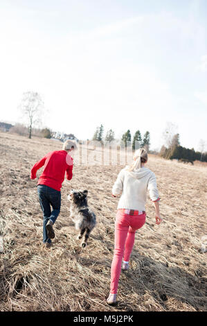 Man and woman with dog running on field - Stock Photo